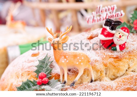 Santa and a reindeer perched on a freshly baked Christmas stollen - stock photo