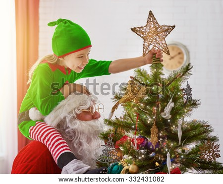 Santa and an elf decorating a Christmas tree. - stock photo