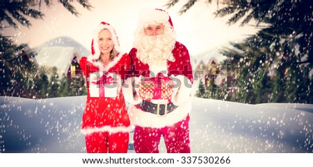 Santa and Mrs Claus smiling at camera offering gift against cute village in the snow - stock photo