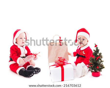 Santa baby girl and boy with gift box and christmas decorations on white - stock photo