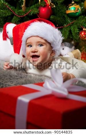 Santa baby near christmas tree - stock photo