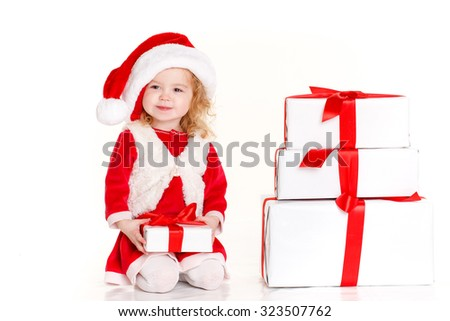 Santa child with christmas gifts isolated on white. Cute little girl in the santa claus hat. Child holding Christmas gift box in hand. Isolated on white background