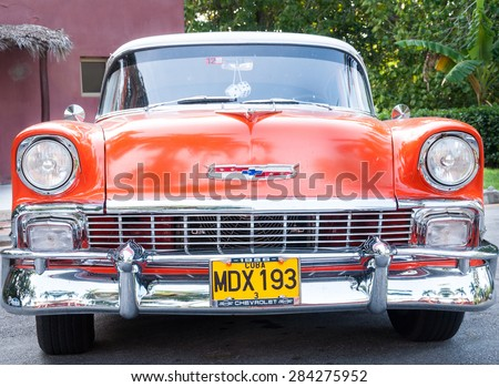 SANTA CLARA,CUBA-AUGUST 10,2014: Orange vintage Chevrolet 57. Old American cars are common in Cuba due lack of supply of modern cars. - stock photo