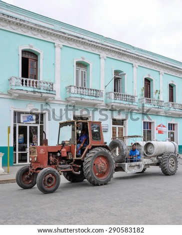 SANTA CLARA,CUBA-JULY 14,2014: Cuban images: Old soviet tractor pulling a trailer on the street Cuban city. Changes in the economic model are happening by the day.