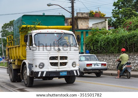 SANTA CLARA,CUBA-JULY 6,2015:Vehicles of all sizes from trucks to motor bikes plying on street.For long time, the embargo on import of cars has force Cubans to repair obsolete vehicles