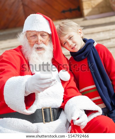 Santa Claus and boy taking selfportrait through smartphone outside house - stock photo