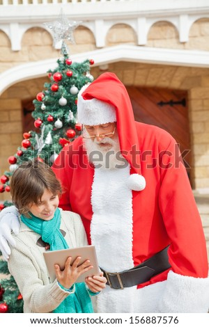 Santa Claus and boy using digital tablet together in front of Christmas tree outdoors - stock photo