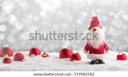 Santa Claus and Christmas balls on snow. - stock photo