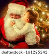 Santa Claus and Little Boy. Christmas Scene. Boy Telling Wish in Santa Claus's Ear in front of Christmas Tree  - stock photo