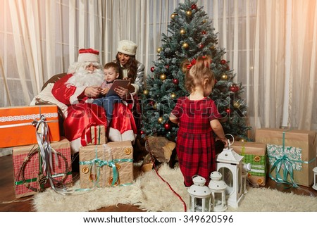 Santa Claus and Snow Maiden give gifts for Christmas - stock photo
