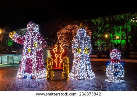 Santa Claus and Snow White statues decorated with lights - stock photo