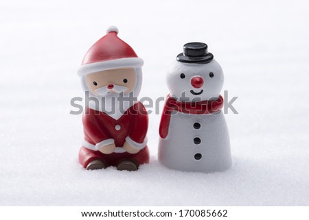 Santa Claus and Snowman figurine in the snow - stock photo