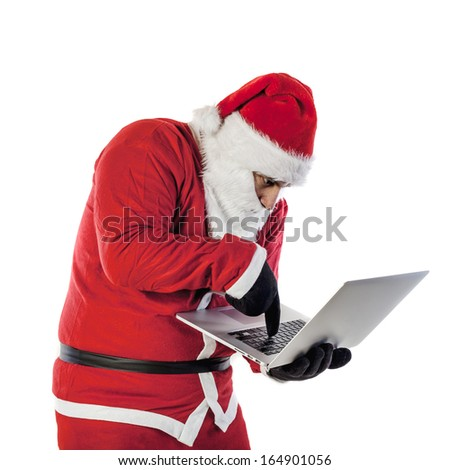 Santa Claus and using a laptop - stock photo