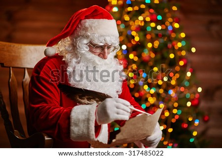 Santa Claus answering Christmas letter by sparkling firtree - stock photo