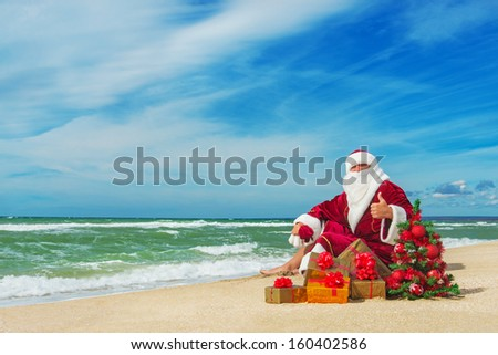 Santa Claus at sea beach with many gifts and decorated christmas tree - happy new year concept - stock photo