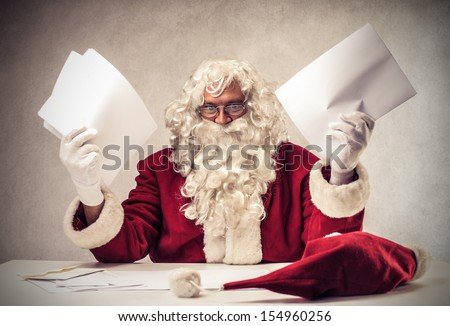 Santa Claus at the office with documents in hand - stock photo
