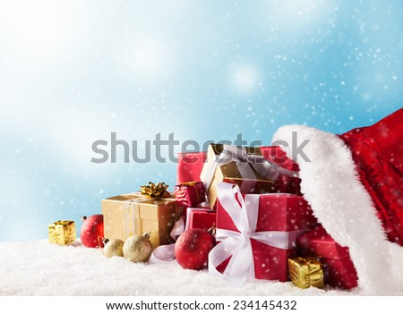 Santa Claus bag full of gifts on snow with blur background - stock photo
