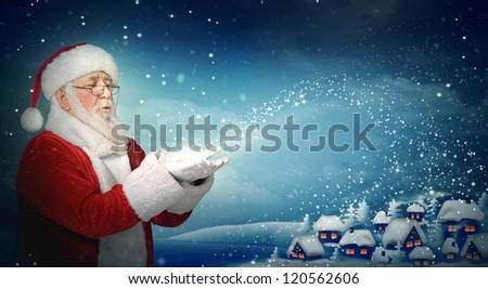 Santa Claus blowing snow to blue  little town at night - stock photo