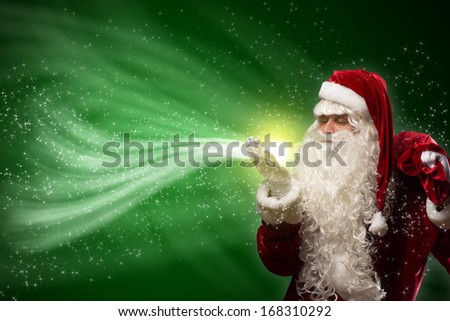 santa claus blows with hands magic sparks holds on shoulder bag with Christmas presents - stock photo