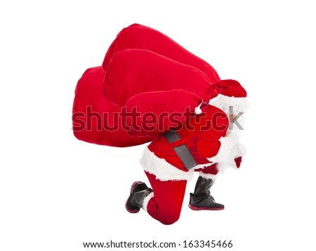 santa claus carrying heavy gift bags - stock photo