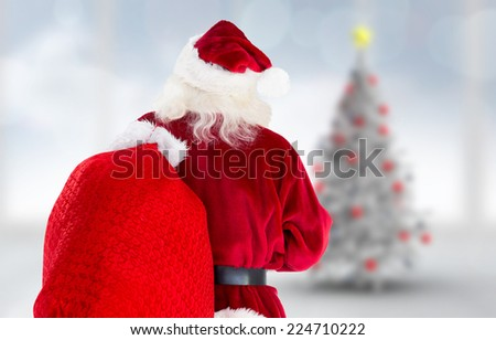 Santa claus carrying sack against blurry christmas tree in room - stock photo