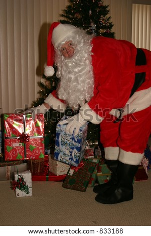 santa claus caught by suprise while placing christmas presents - stock photo
