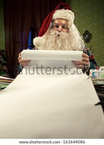 Santa Claus checking his Christmas list - stock photo