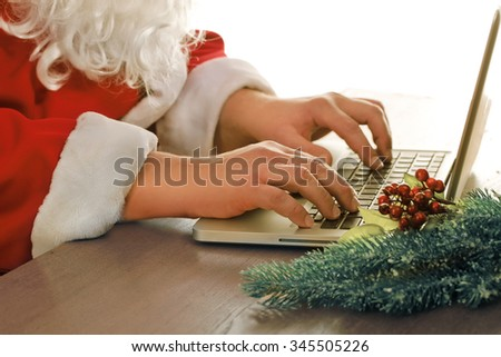 Santa Claus, chris mas tree    and computer - stock photo