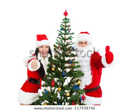 Santa Claus christmas girl hold hand show thumb up finger gesture with green decorated tree, isolated on white background, happy new year