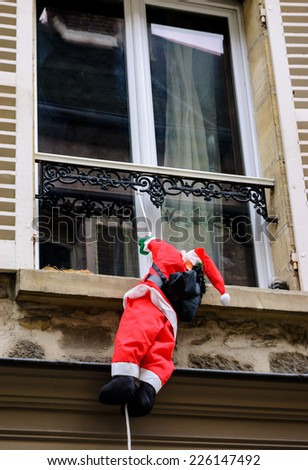 Santa Claus climbing up a wall into a window. Traditional Christmas decoration. - stock photo