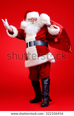 Santa Claus comes with a big bag of gifts. Full length portrait. - stock photo