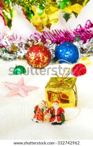 Santa claus dall and gold gift, Christmas decoration on white wool. Decoration of X'mas and New Year Celebration. Selective focus on a gift. - stock photo
