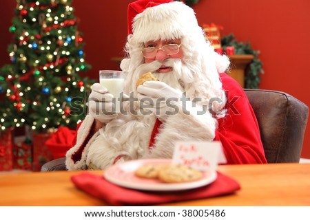 Santa Claus eating cookies with glass of milk