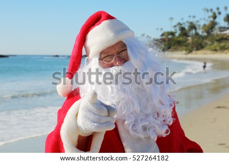 Santa Claus enjoys a Day at the Beach. Santa loves the ocean. Santa Claus in the sand. Christmas vacation.