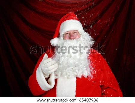 Santa Claus enjoys fresh falling snow while he prepairs for the Christmas Rush - stock photo