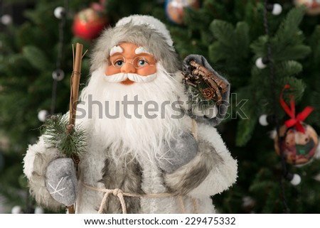 Santa Claus figurine on New Years Eve 2015 standing against the background of a decorated Christmas tree.