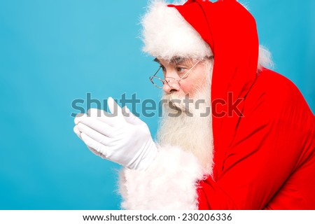 Santa claus getting ready to blow snow from his hand - stock photo