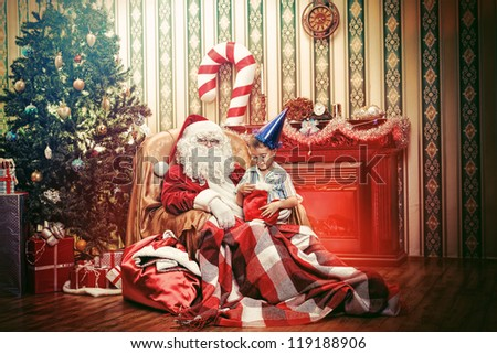 Santa Claus giving a present to a little cute boy at home. - stock photo