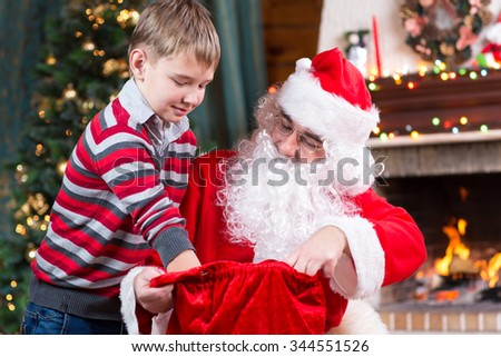 Santa Claus giving a present to child boy near the fireplace and Christmas tree at home. - stock photo