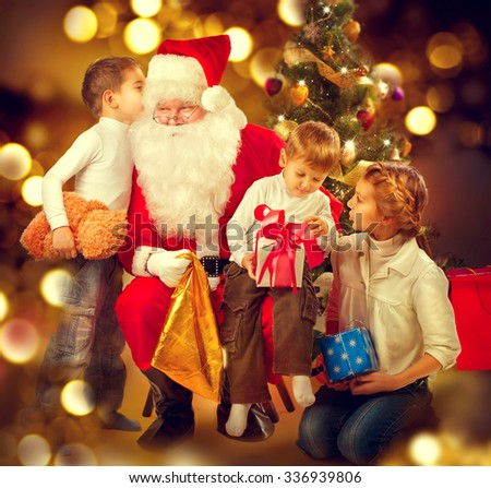 Santa Claus giving Christmas gifts to children. Santa and Happy Kids - Sister and Brothers. Cute little Boys and Santa Claus holding Giftbox. Christmas Holiday Scene over Decorated Christmas Tree - stock photo