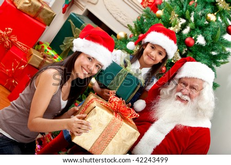 Santa Claus giving presents to some girls - stock photo