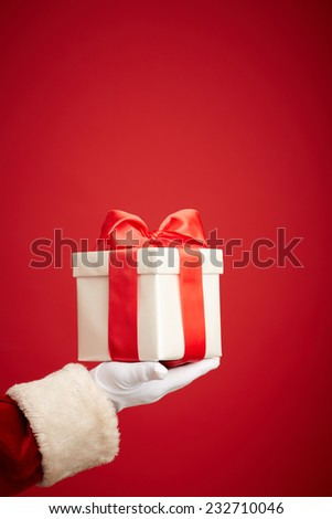 Santa Claus gloved hand holding giftbox with red bow - stock photo