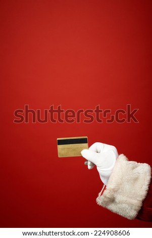 Santa Claus gloved hand holding plastic card over red background - stock photo