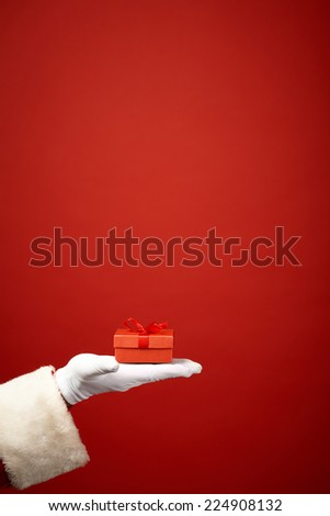 Santa Claus gloved hand with small package over red background - stock photo