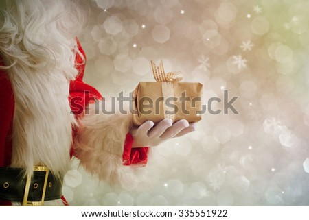 Santa Claus gloved hands holding giftbox - stock photo