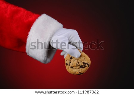 Santa Claus hand holding a chocolate chip cookie over a light to dark red background. Horizontal format showing only hand and arm. - stock photo