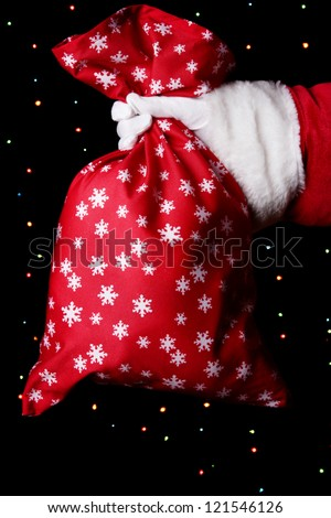 Santa Claus hand holding bag of gifts on bright background - stock photo