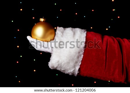 Santa Claus hand holding christmas ball on bright background