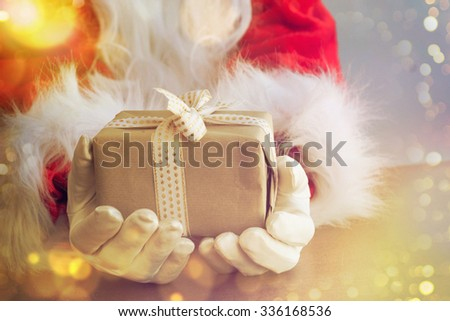 Santa Claus hand holding gift - stock photo