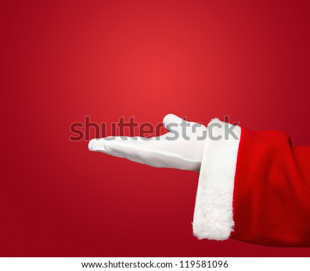 Santa Claus hand presenting your christmas text or product over red background with copy space